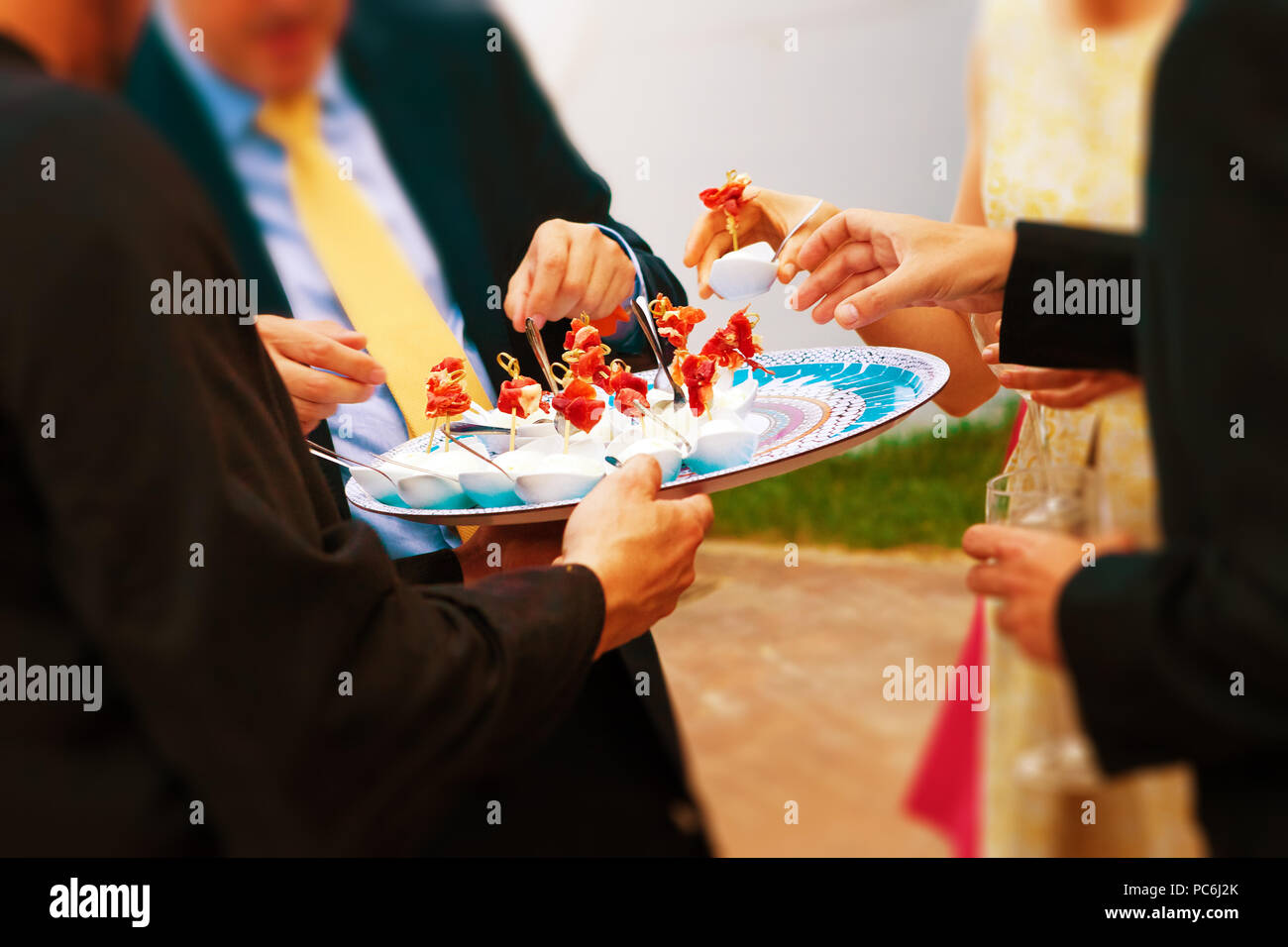 Food and catering. Wedding celebration and banquet. Wedding guests eating an appetizer - Stock Image
