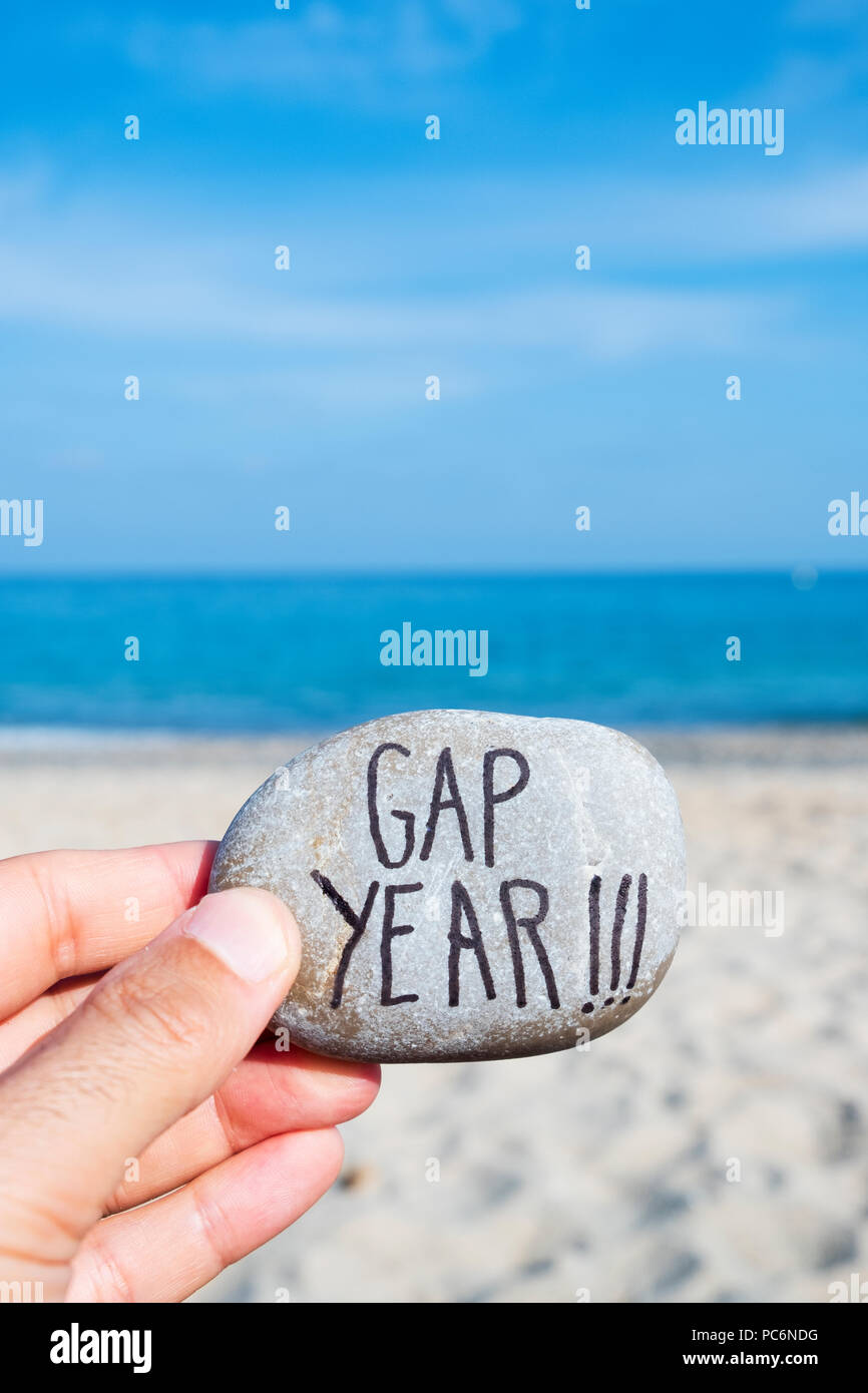closeup of the hand of a young caucasian man on the beach, in front of the ocean, holding a stone with the text gap year written in it - Stock Image