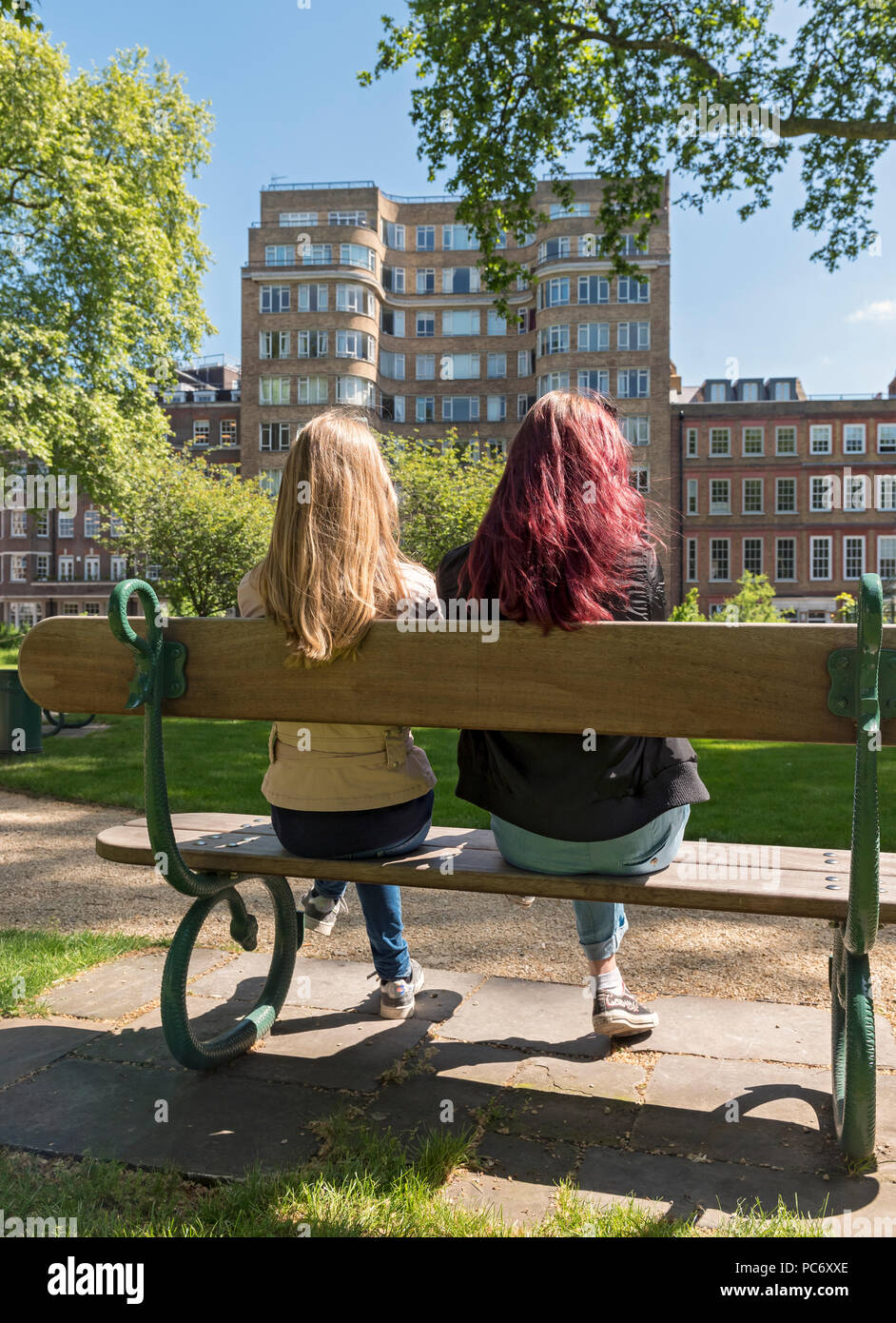 Two girls sit on a bench outside Florin Court building aka Whitehaven Mansions residence of Hercule Poirot,  Charterhouse Sq, London, England, UK - Stock Image