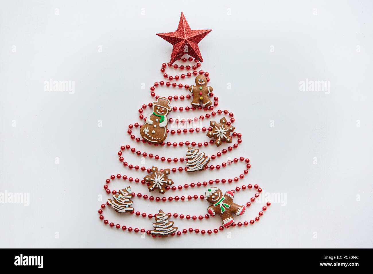 creative idea in minimalistic style for christmas or new year themes a christmas tree made of beads decorated with ginger cookies and a star on top