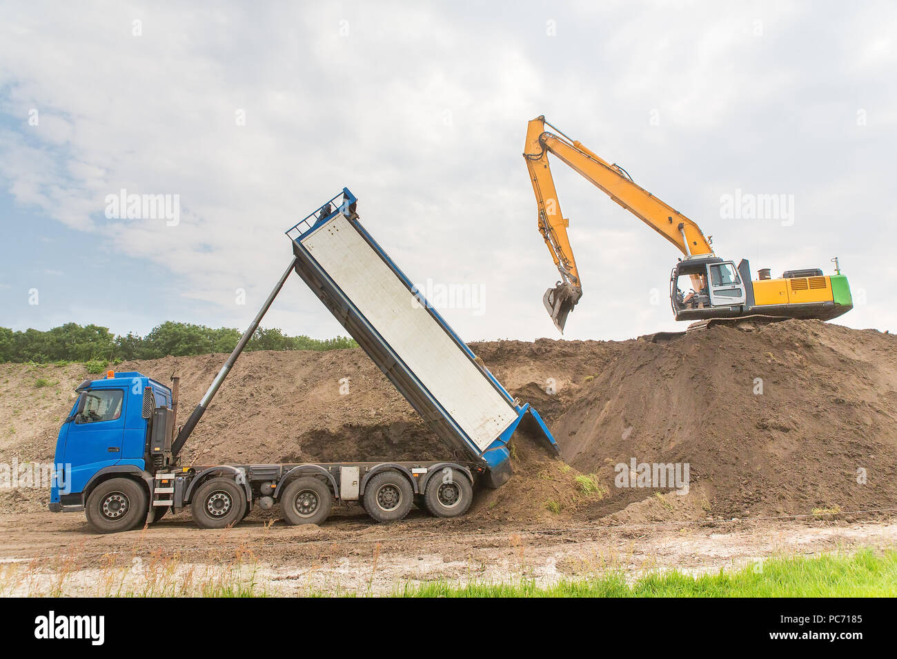 Truck and excavator together build a sound barrier of sand - Stock Image