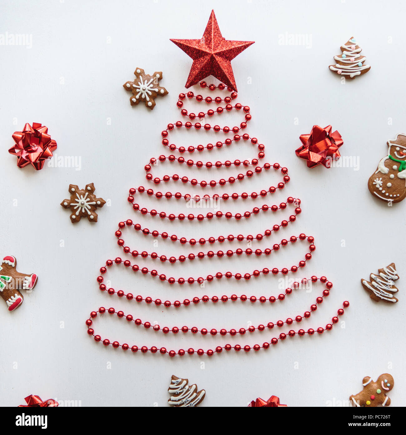creative idea for christmas or new year theme a christmas tree made of beads and a star on top next to it lie the traditional gingerbread