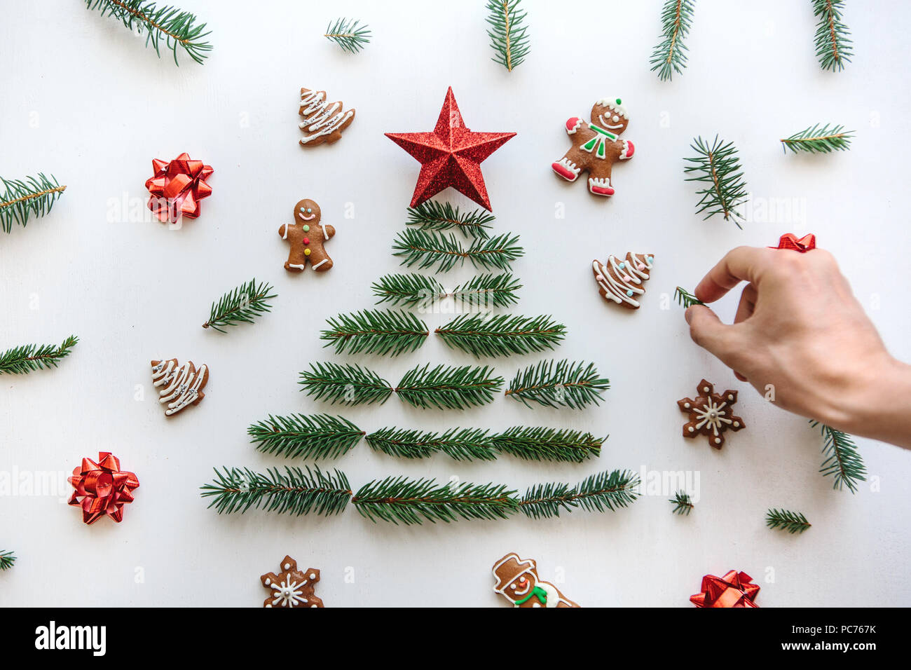 creative idea for christmas or new year theme a person makes a creative christmas tree from fir branches and a star on top and is decorated with