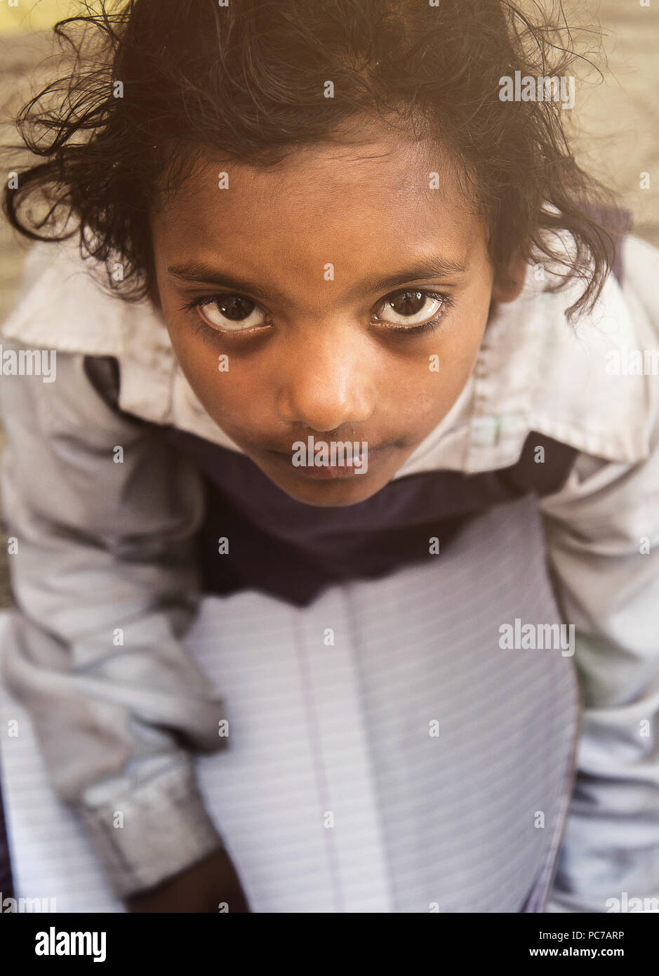 Village school girl portrait in school uniform. She is sitting on mat of her classroom floor holding school notebook in her lap for class assignments. Stock Photo