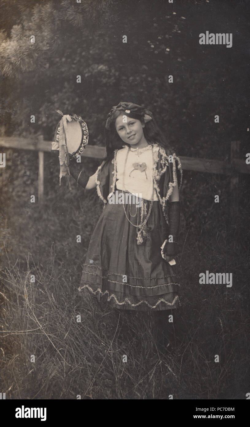 Vintage 1912 Photograph of a Girl Named as Nora Squires Dressed In Theatrical Costume Holding a Tambourine - Stock Image