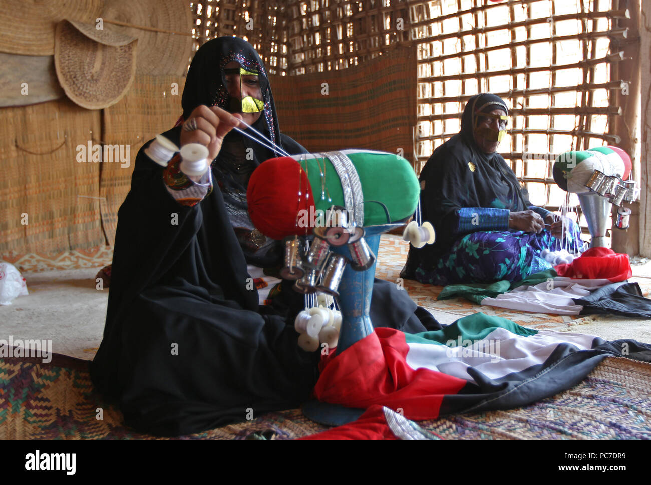 A woman sporting a metallic burqa knits Emirati flag in the heritage village in Fujairah. The village is place to items showing Emirati culture. Stock Photo
