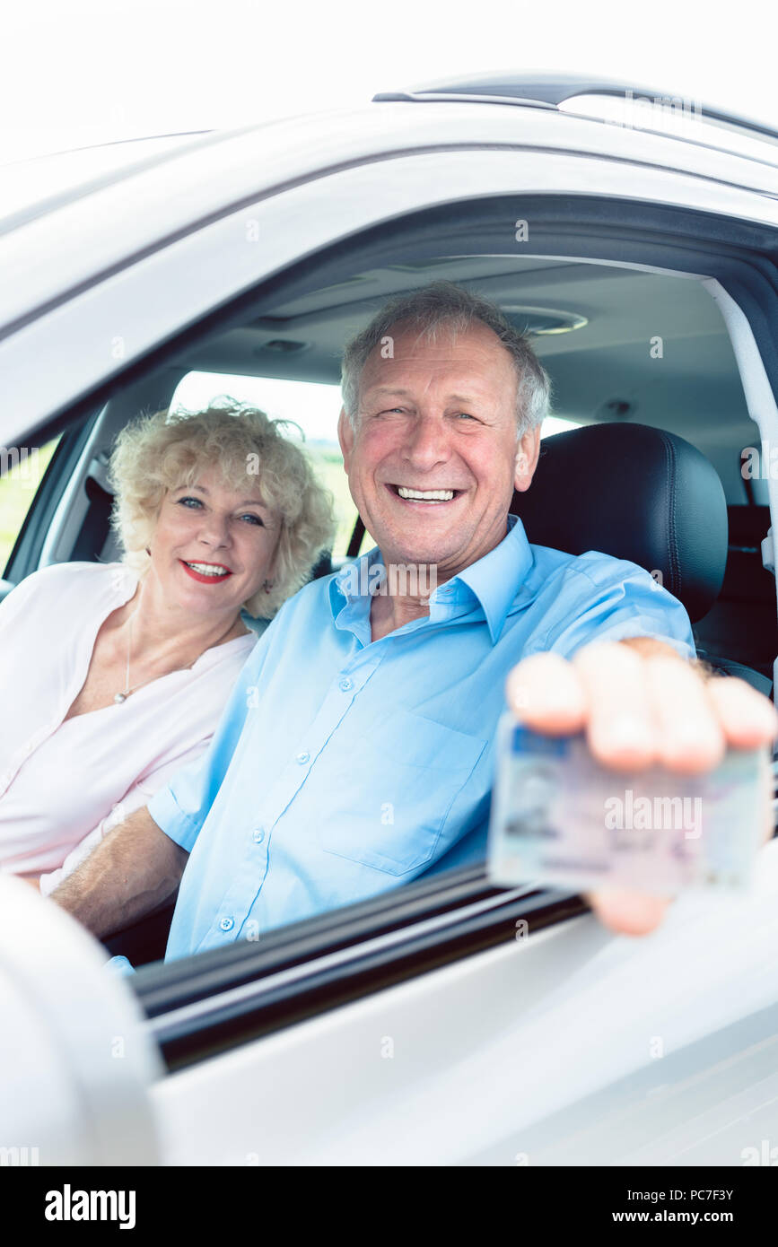 Portrait of a happy senior man showing his driving license Stock Photo