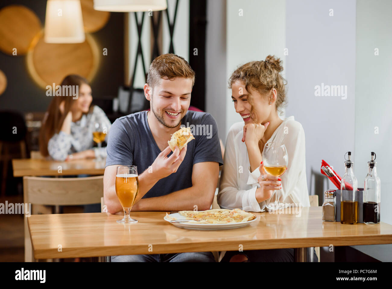 Interior of modern pizzeria. Sweet couple sitting near table, smiling and posing. Beautiful woman with curly hair and handsome man eating pizza. Pizza and glasses of wine and beer on table. - Stock Image
