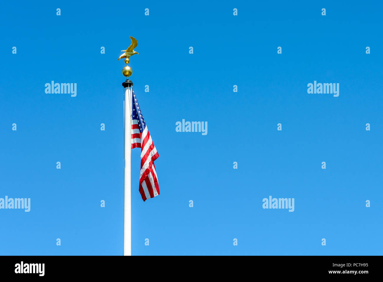 The flag of the United States of America dangling at full-mast on a white pole topped with a golden eagle on ball ornament against deep blue sky. - Stock Image