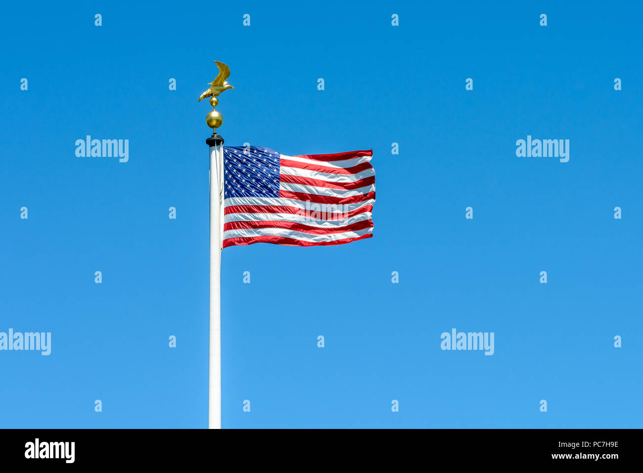 The flag of the United States of America blowing in the wind at full-mast on a pole topped with a golden eagle on ball ornament against deep blue sky. - Stock Image