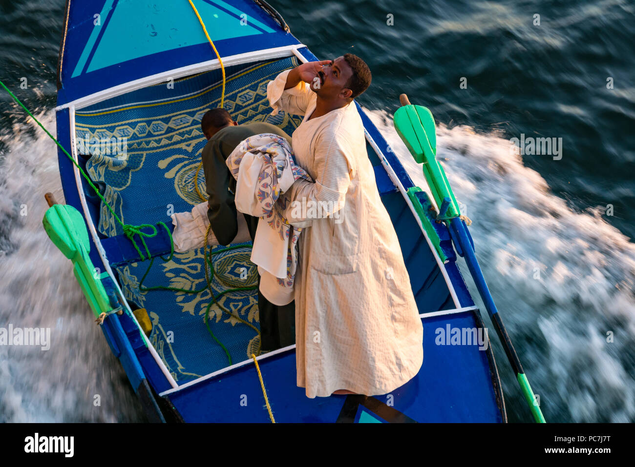 Local Egyptian men hawkers in small wooden boat tied to cruise ship selling linen products, River Nile, Egypt, Africa - Stock Image
