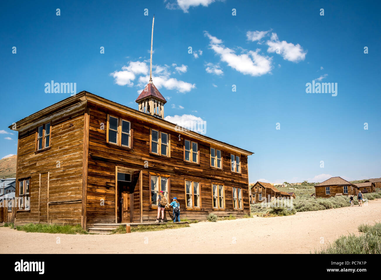 Tourists peer into an old abandoned school building in Bodie, California State Historic Park, which once was a mining boom town in the eastern Sierra - Stock Image