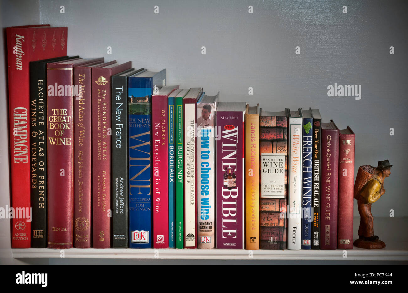 WINE BOOKS VINTAGES GRAPES GEOGRAPHY Variety of classic and contemporary wine reference books on bookshelf with carved grape harvester bookend figure - Stock Image