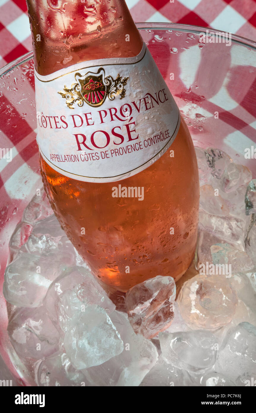 Côtes de Provence rosé bottle chilling in alfresco ice wine cooler on typical French style tablecloth - Stock Image