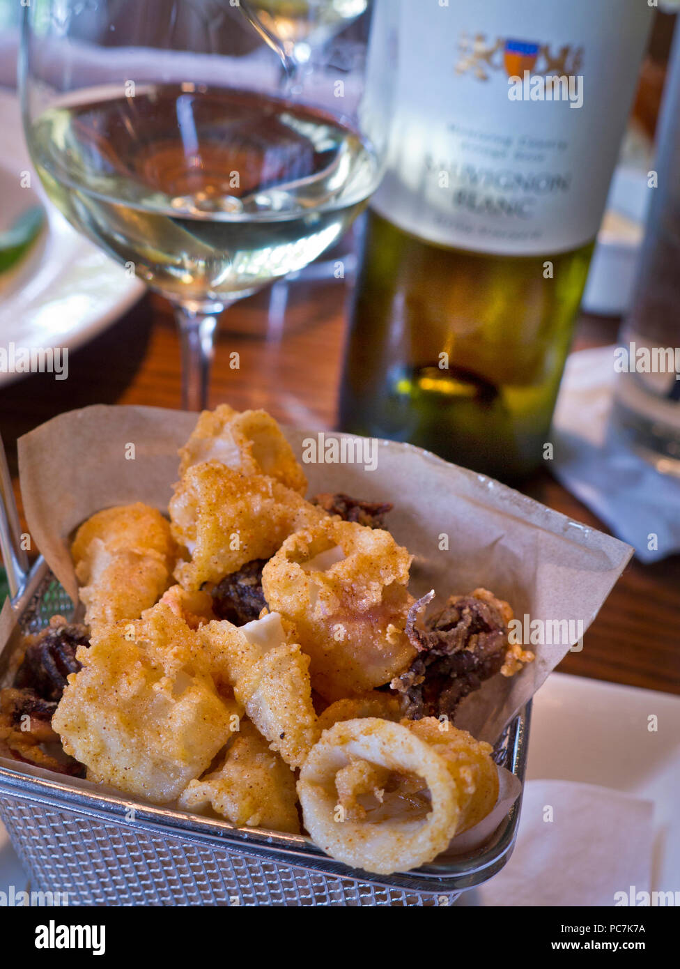 Fried calamari squid tapas basket with glass of white dry Californa Bernardus Sauvignon Blanc in renowned Rio Grill restaurant Carmel California USA - Stock Image