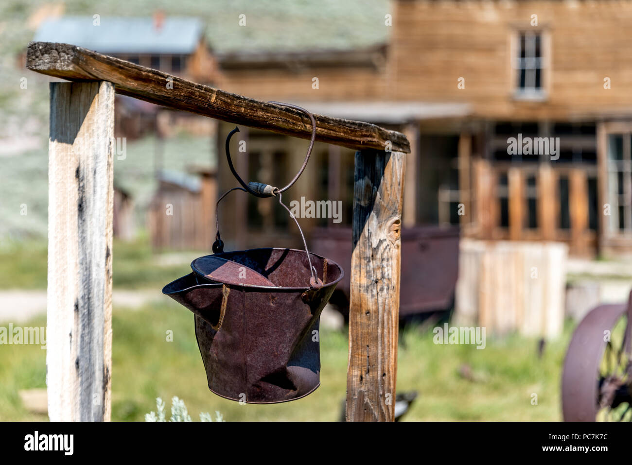 A rusty pail hangs above a one-time well in the abandoned California ghost town of Bodie, now a state historic park in the eastern Sierra Mountains. - Stock Image