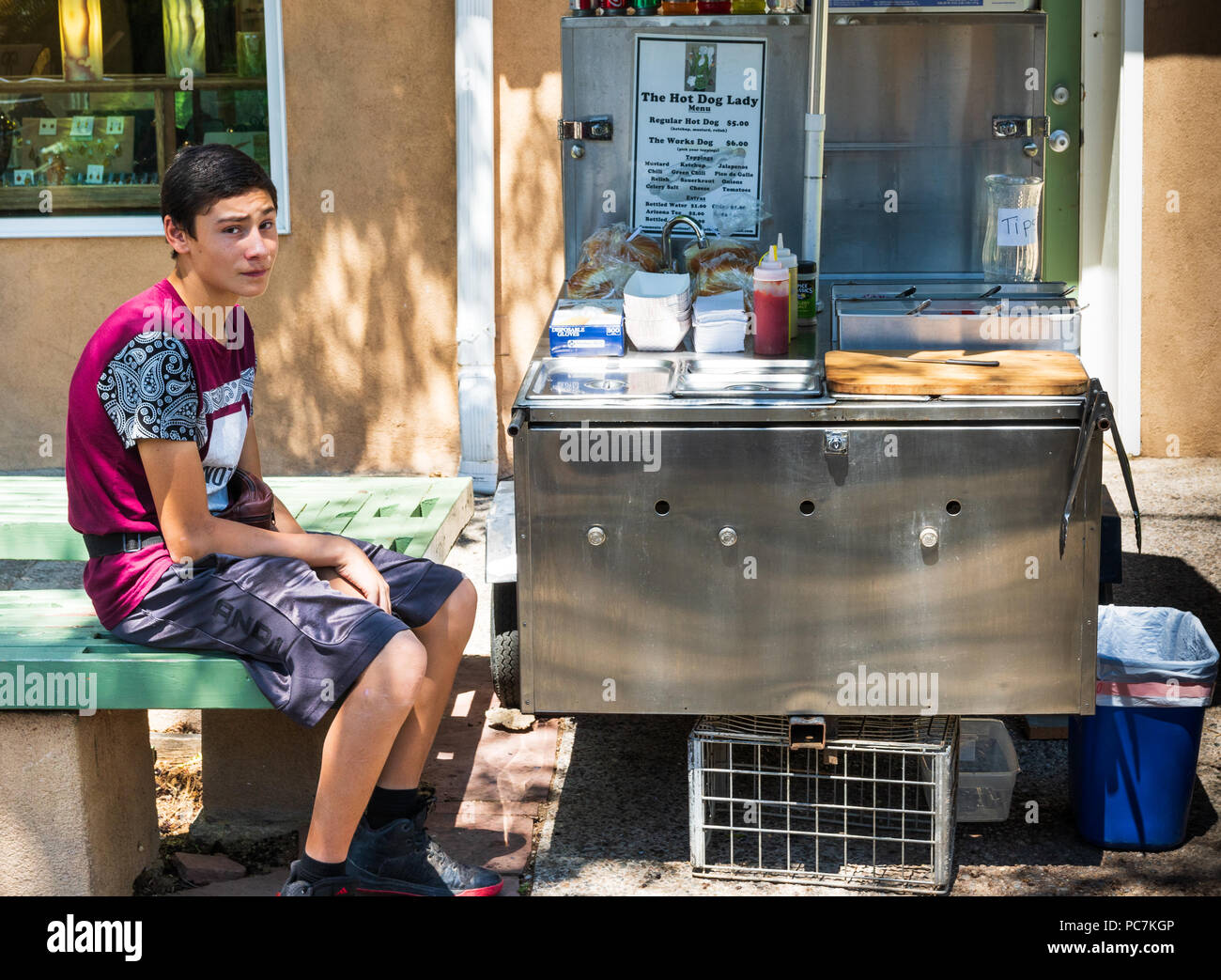 TAOS, NM, USA-8 JULY 18: A forlorn-looking teenaged boy, sitting beside his hot dog stand on Bent St. in Taos,  waiting for customers to appear. - Stock Image