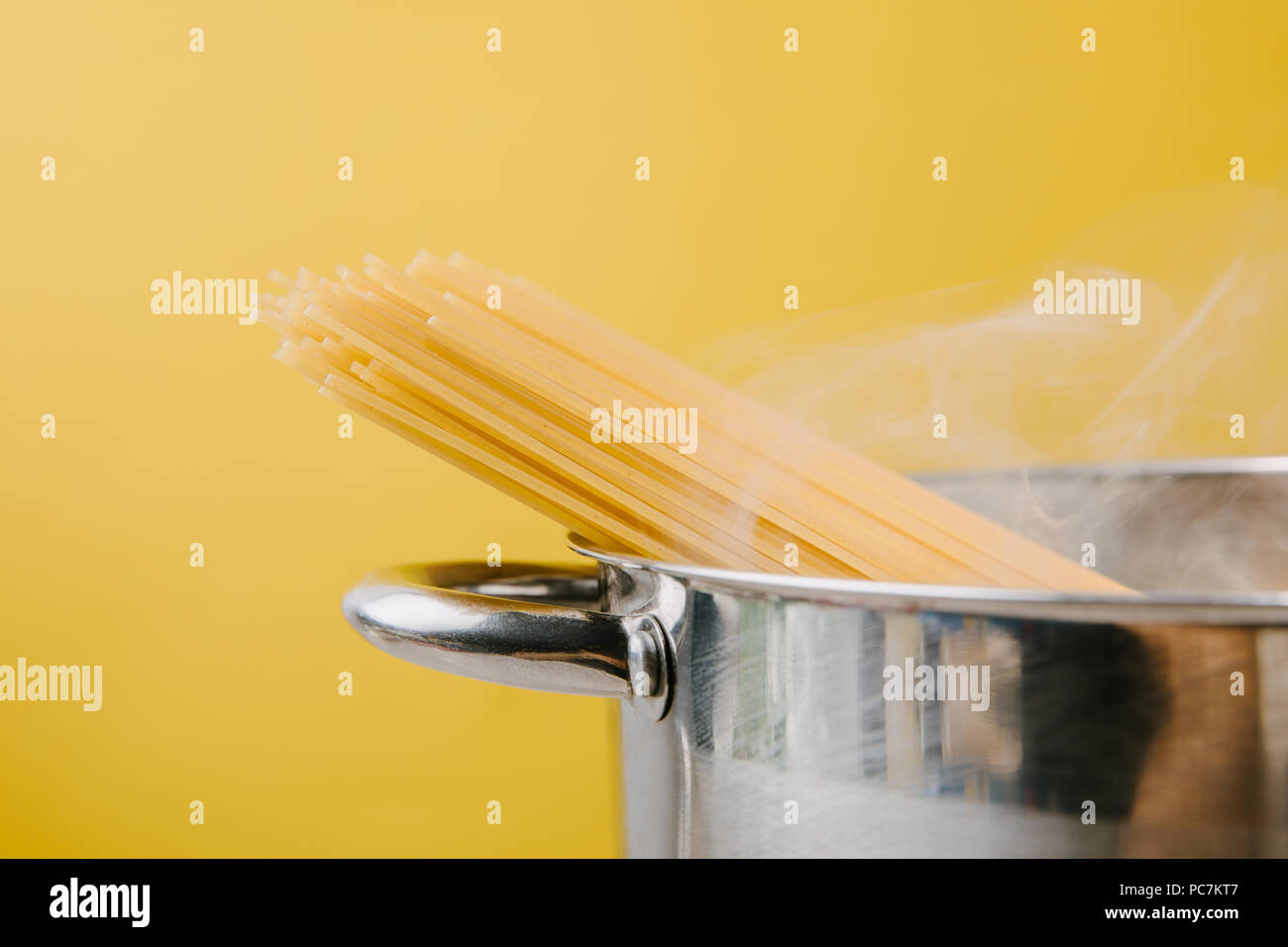 spaghetti boiling in stewpot isolated on yellow - Stock Image
