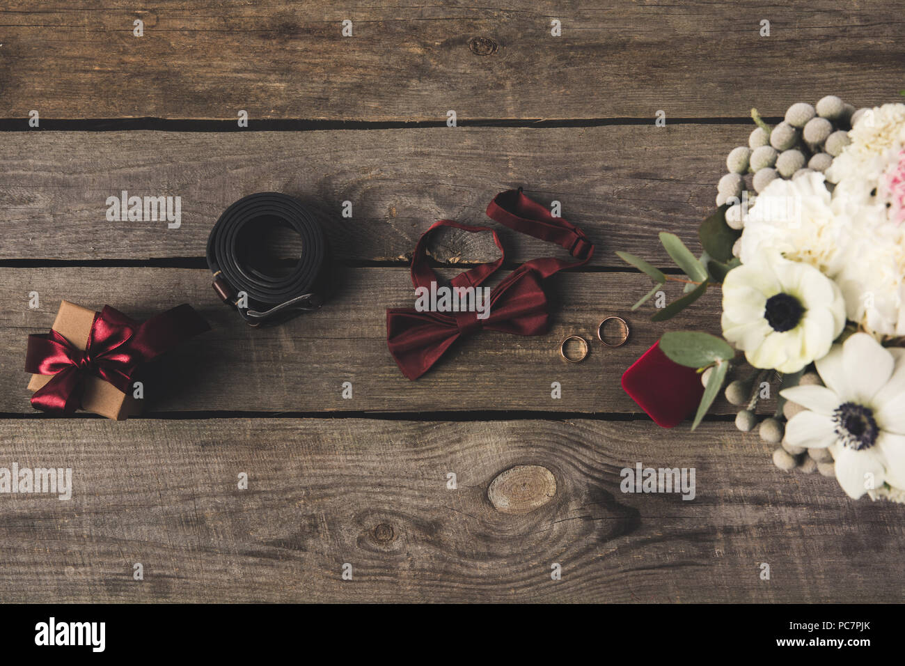 Flat lay with wedding rings jewelry box bridal bouquet gift and flat lay with wedding rings jewelry box bridal bouquet gift and grooms accessories on wooden tabletop junglespirit Image collections