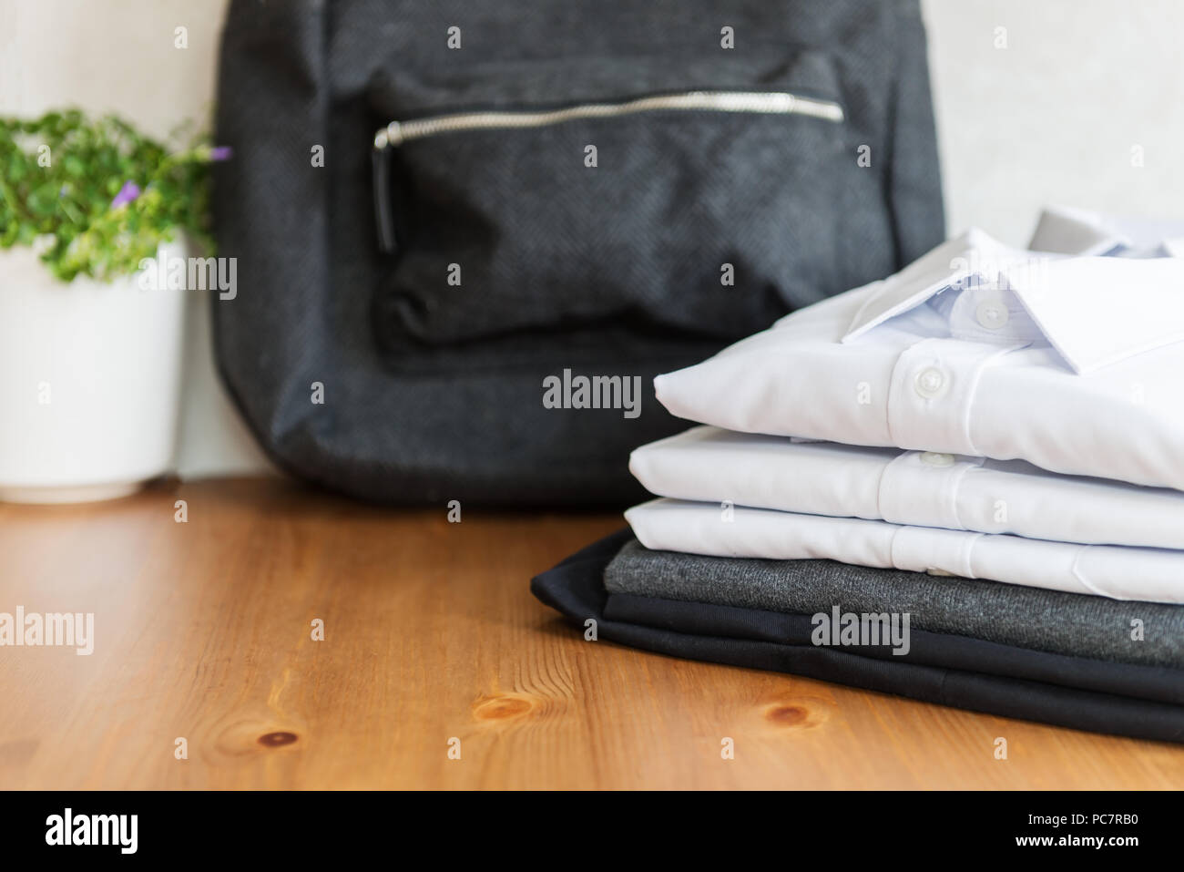 Back to school concept, backpack, school uniform such as white shirts, sweater and trousers on the light background - Stock Image