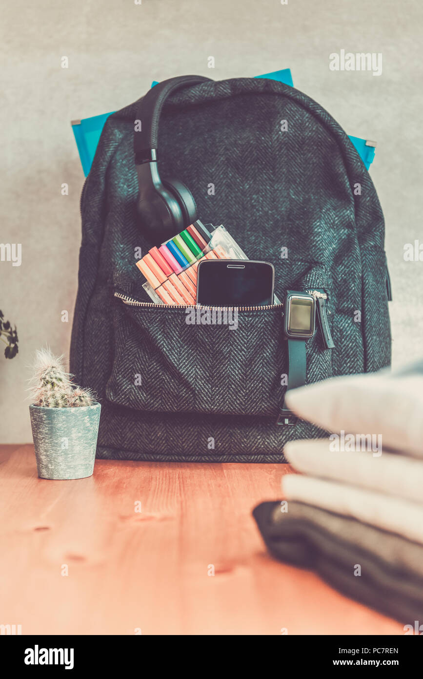 Back to school concept, backpack with school uniform such as white shirts and sweater, as well as electronic devices such as smart watch, mobile phone - Stock Image