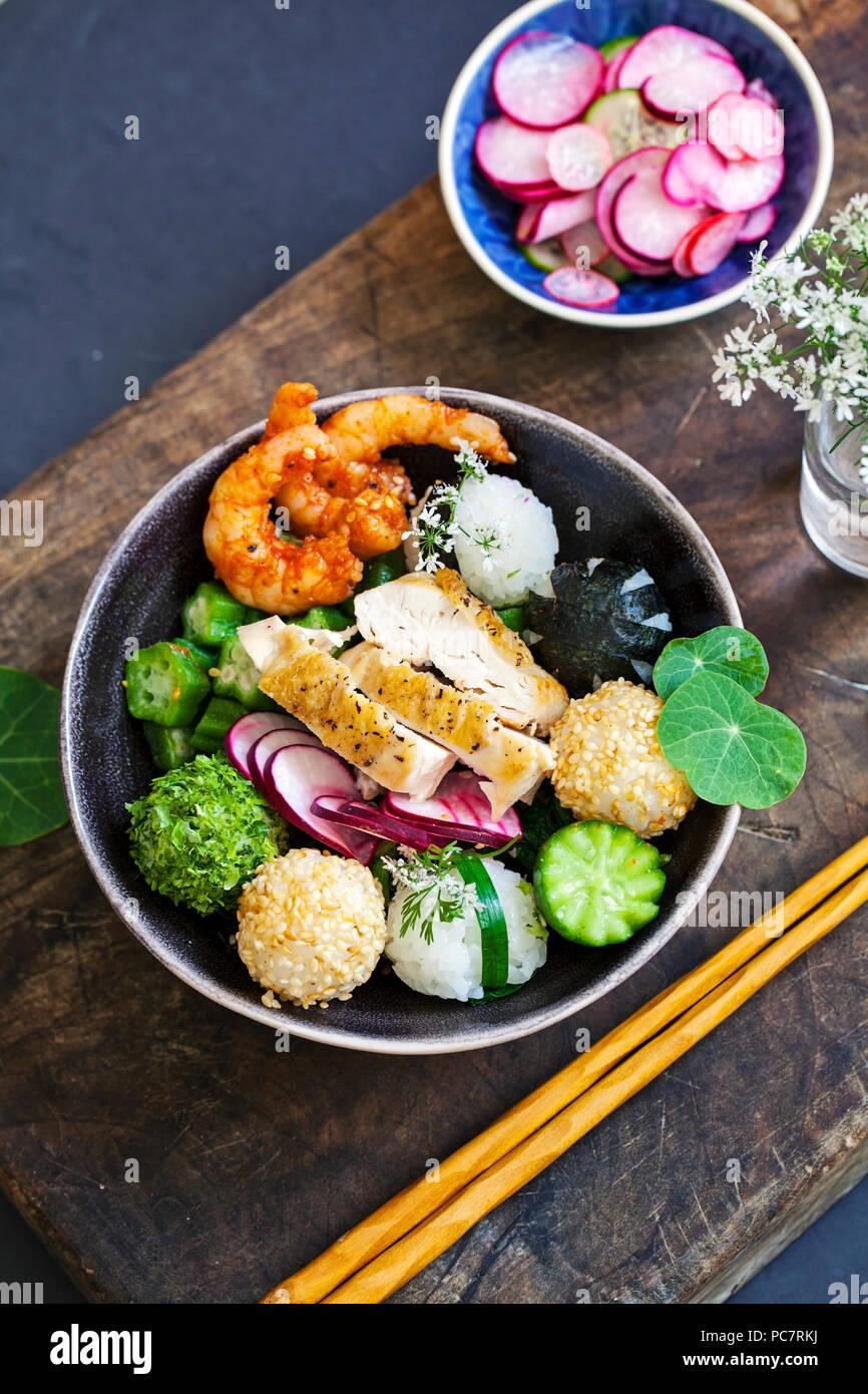 Bento box with onigiri, prawns and vegetables - Stock Image