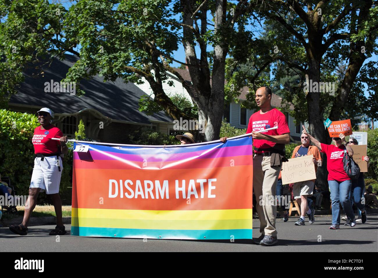 Anti-gun activists holding a 'disarm hate' banner, at the Eug Parade in Eugene, Oregon, USA. - Stock Image