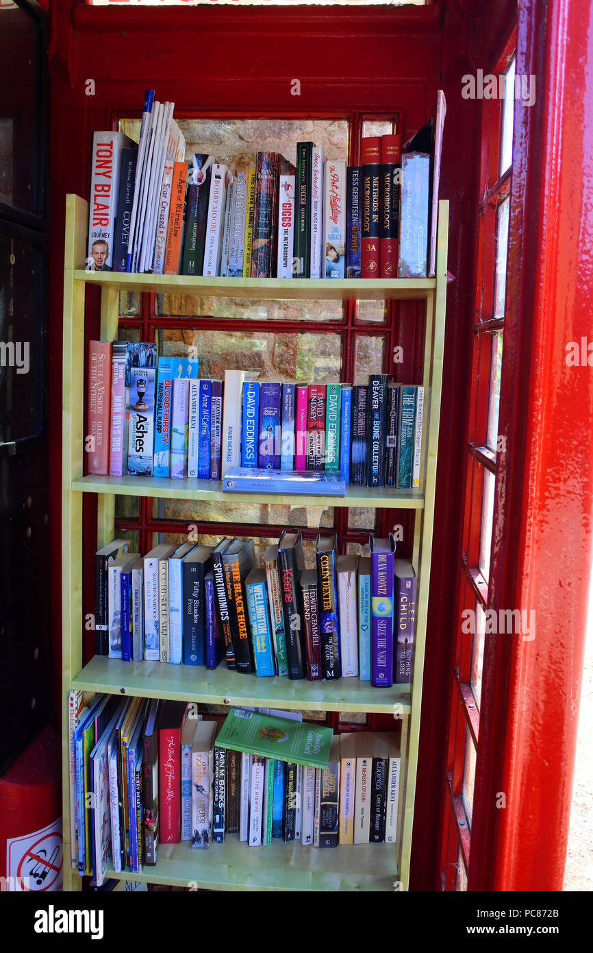 Red telephone kiosk being used as a community book exchange - John Gollop - Stock Image