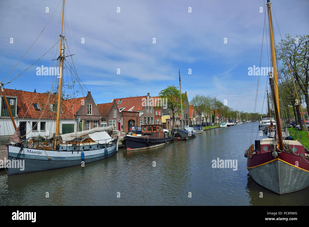 Sailing boats along a canal in the  pretty Dutch small town of Edam well known for its cheese making, Holland, The Netherlands - Stock Image