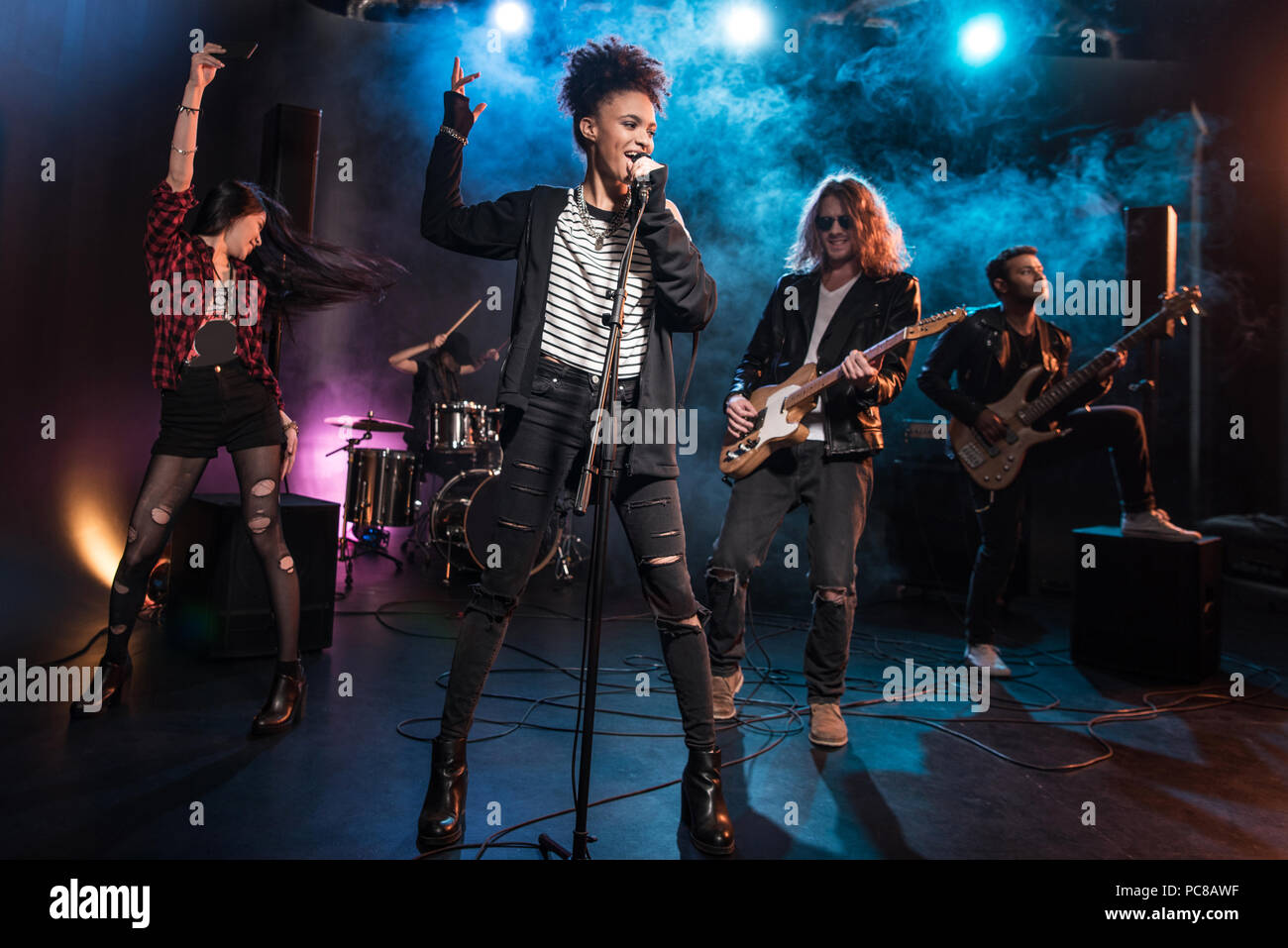 Female Singer With Microphone And Rock And Roll Band Performing Hard Rock Music On Stage Stock Photo Alamy