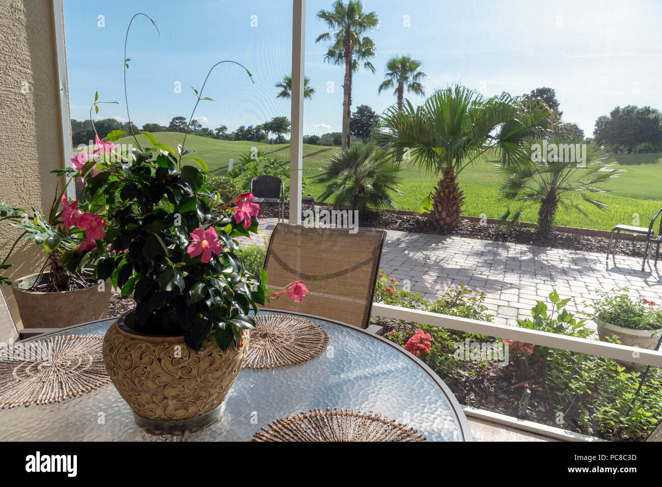 View from a lanai patio through an insect screening onto a golf course. Florida, USA - Stock Image