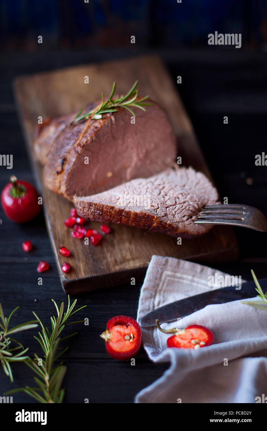 baked meat with rosemary and red pepper. steak. beef. dinner for men. dark photo. Black background. wooden board. - Stock Image