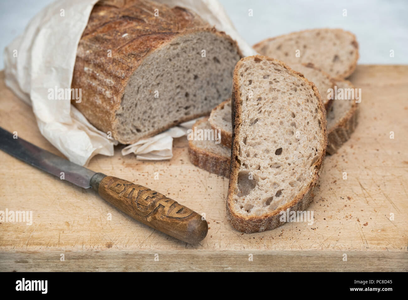 Sourdough bread with a vintage bread knife on a bread board. UK Stock Photo
