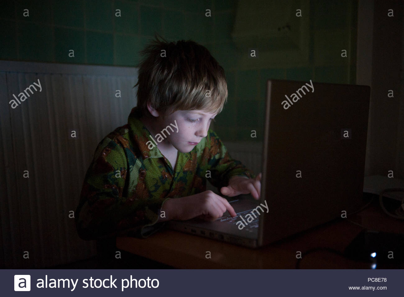A 7-year-old boy stays up late playing computer games. - Stock Image