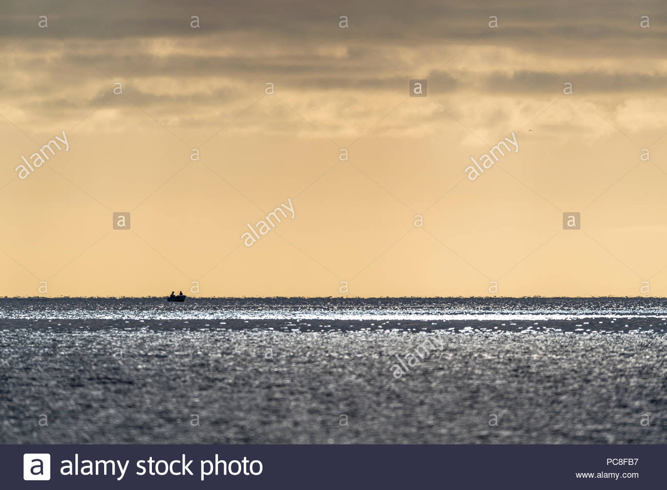 Fishermen on a boat at sunrise in Port Philip Bay. - Stock Image