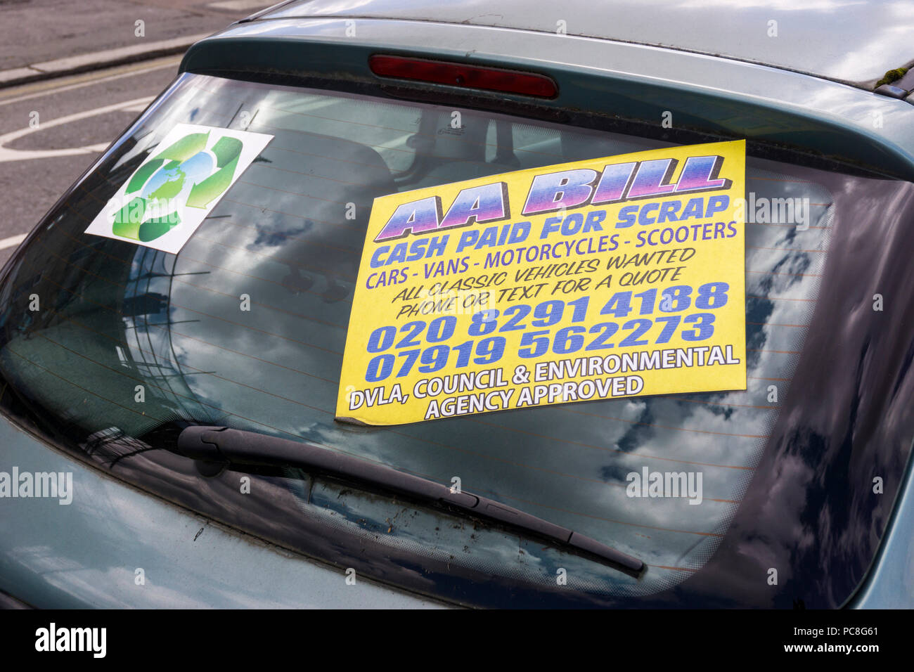 A sign in a car window in south London offers to pay cash for scrap cars, vans, motorcycles and scooters. - Stock Image