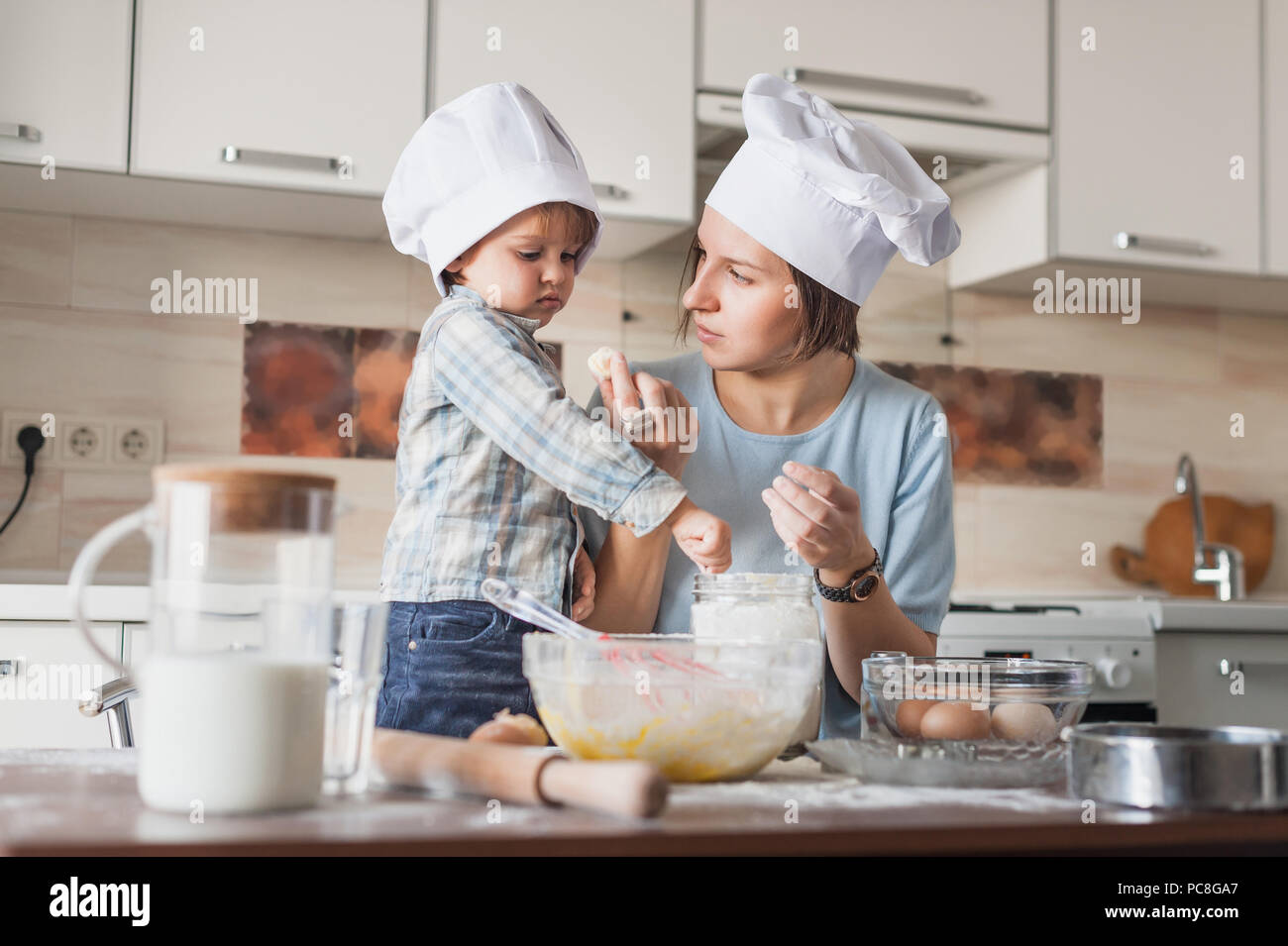 mother teaching her child how to prepare dough at kitchen - Stock Image