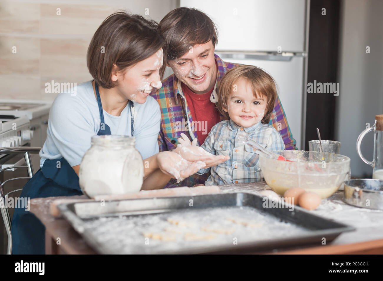 happy young family cooking with floor together at kitchen - Stock Image