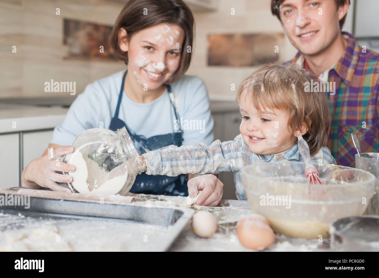 adorable little kid helping his parents with cooking at kitchen - Stock Image