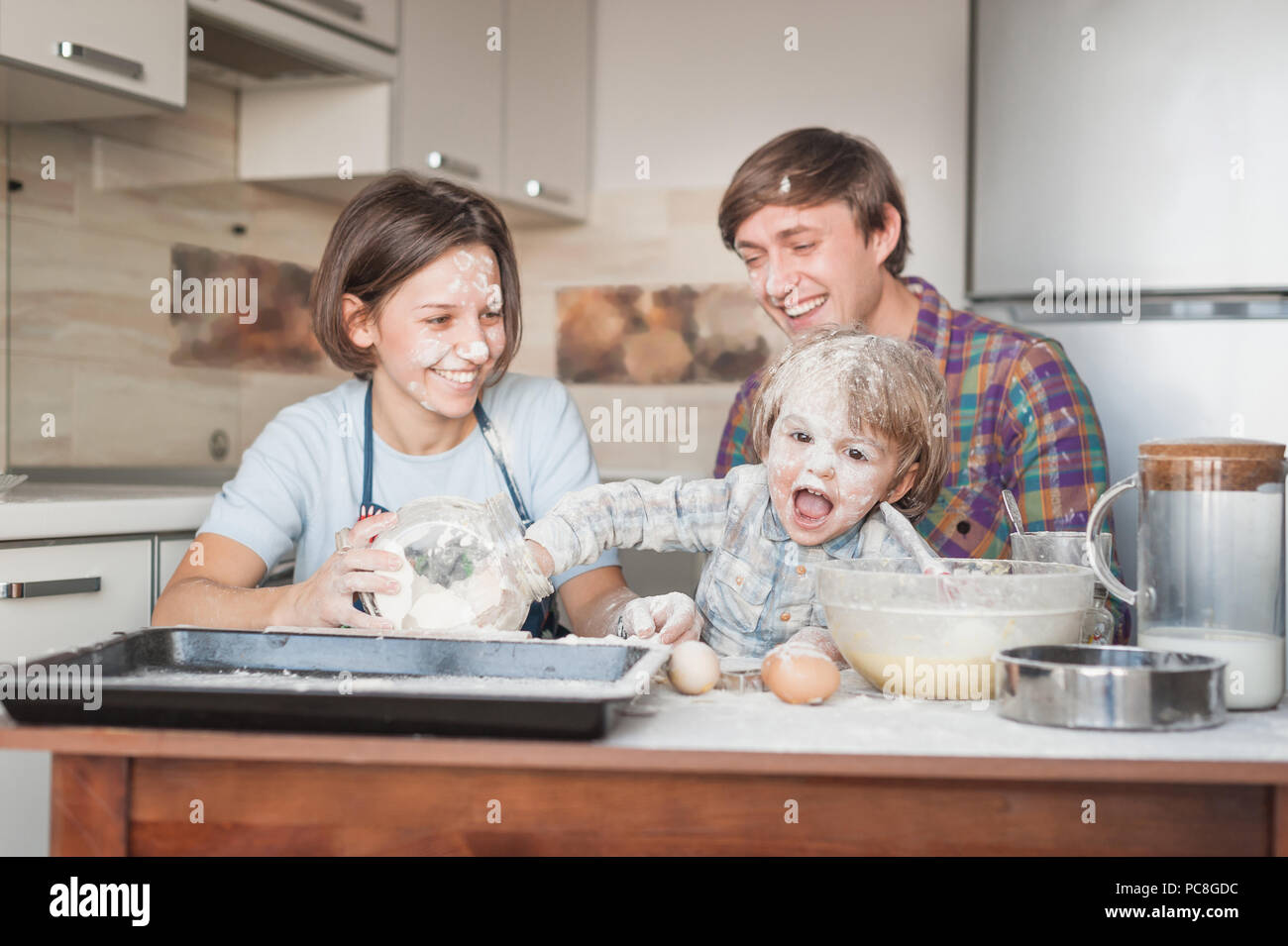 dirty young family cooking with flour together at kitchen - Stock Image