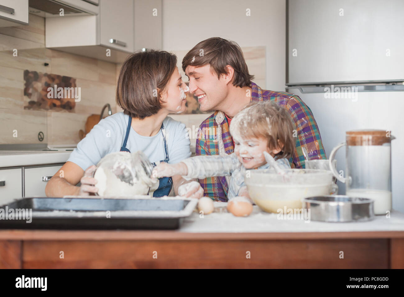beautiful young family cooking with flour together at kitchen - Stock Image