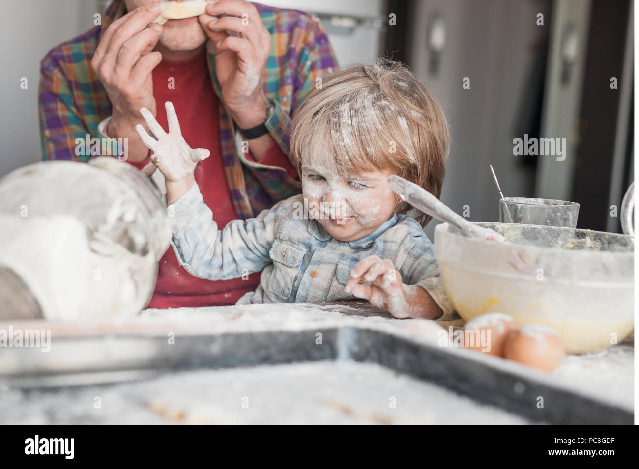 father and child having fun with flour at kitchen - Stock Image