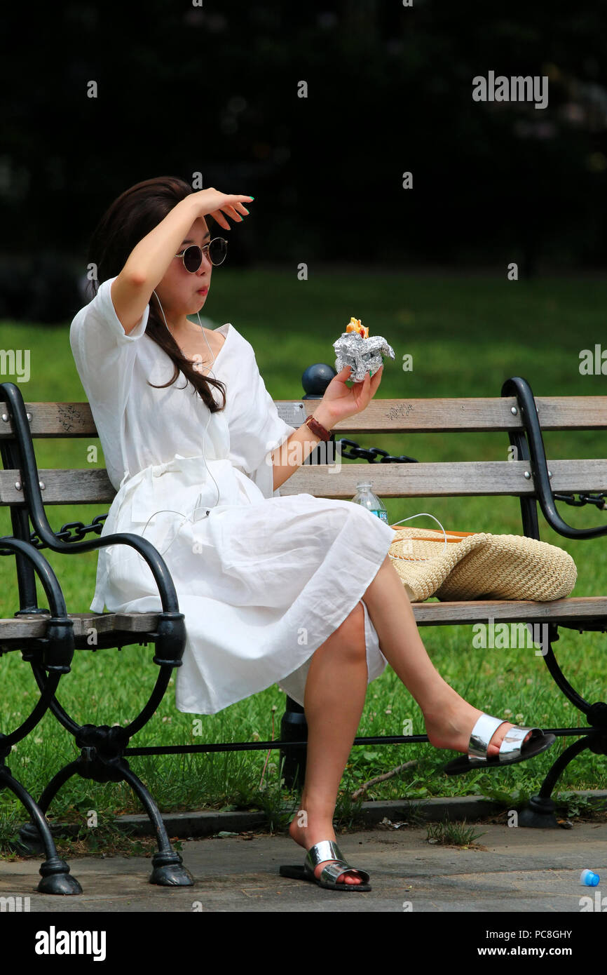 NEW YORK, NY - JULY 10: Young asian woman eats a snack on a hot summer day in Washington Square Park in Manhattan on JULY 10th, 2017 in New York, USA. Stock Photo