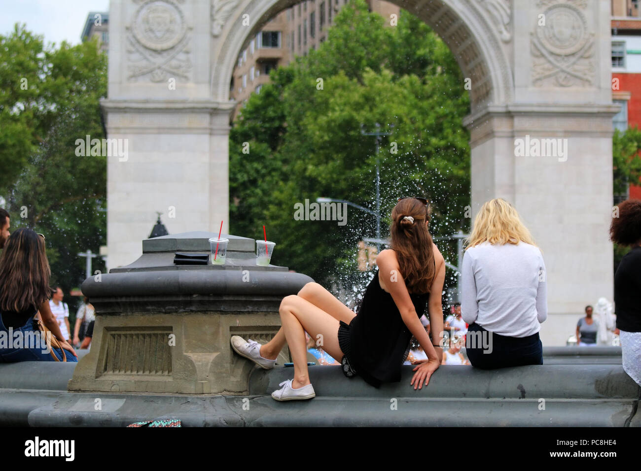 NEW YORK, NY - JULY 10: Young women sit on a rim of a Washington Square Park fountain in Manhattan on JULY 10th, 2017 in New York, USA. - Stock Image