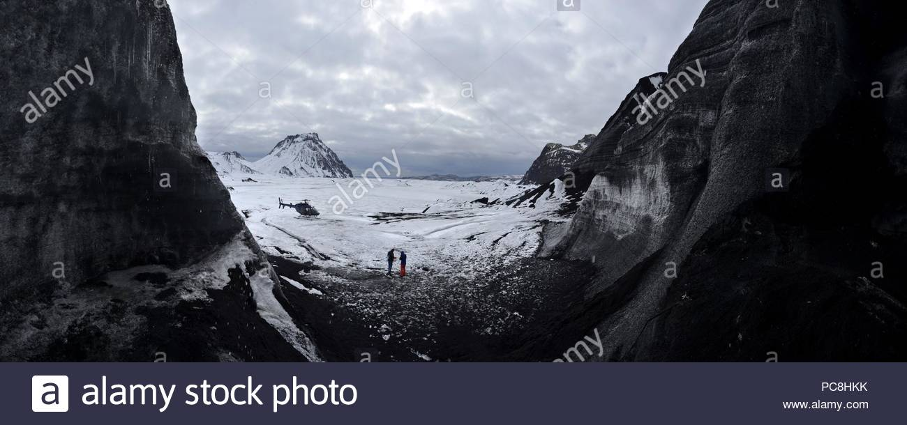Panoramic image of a helicopter outside of ice cave in Kotlujokull glacier in Iceland. - Stock Image