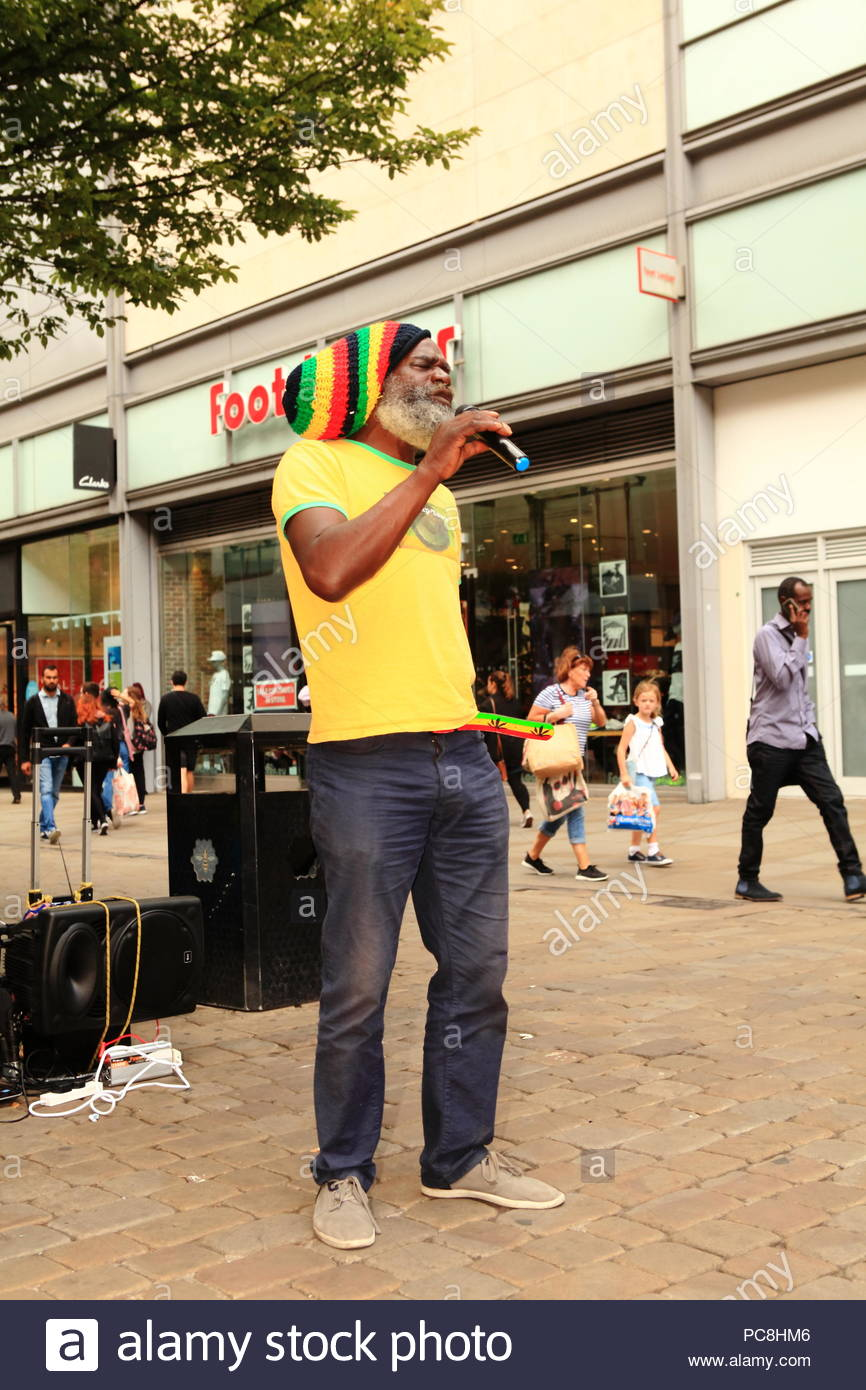 A Rastafarian street artist performing Bob Marley songs at Manchester City Centre UK Summer August 2018 - Stock Image