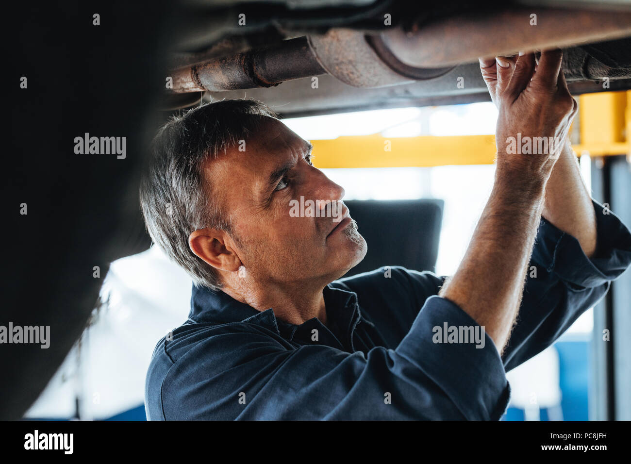 Portrait of a mechanic at work in his garage. Mature auto technician working under a car service station. - Stock Image