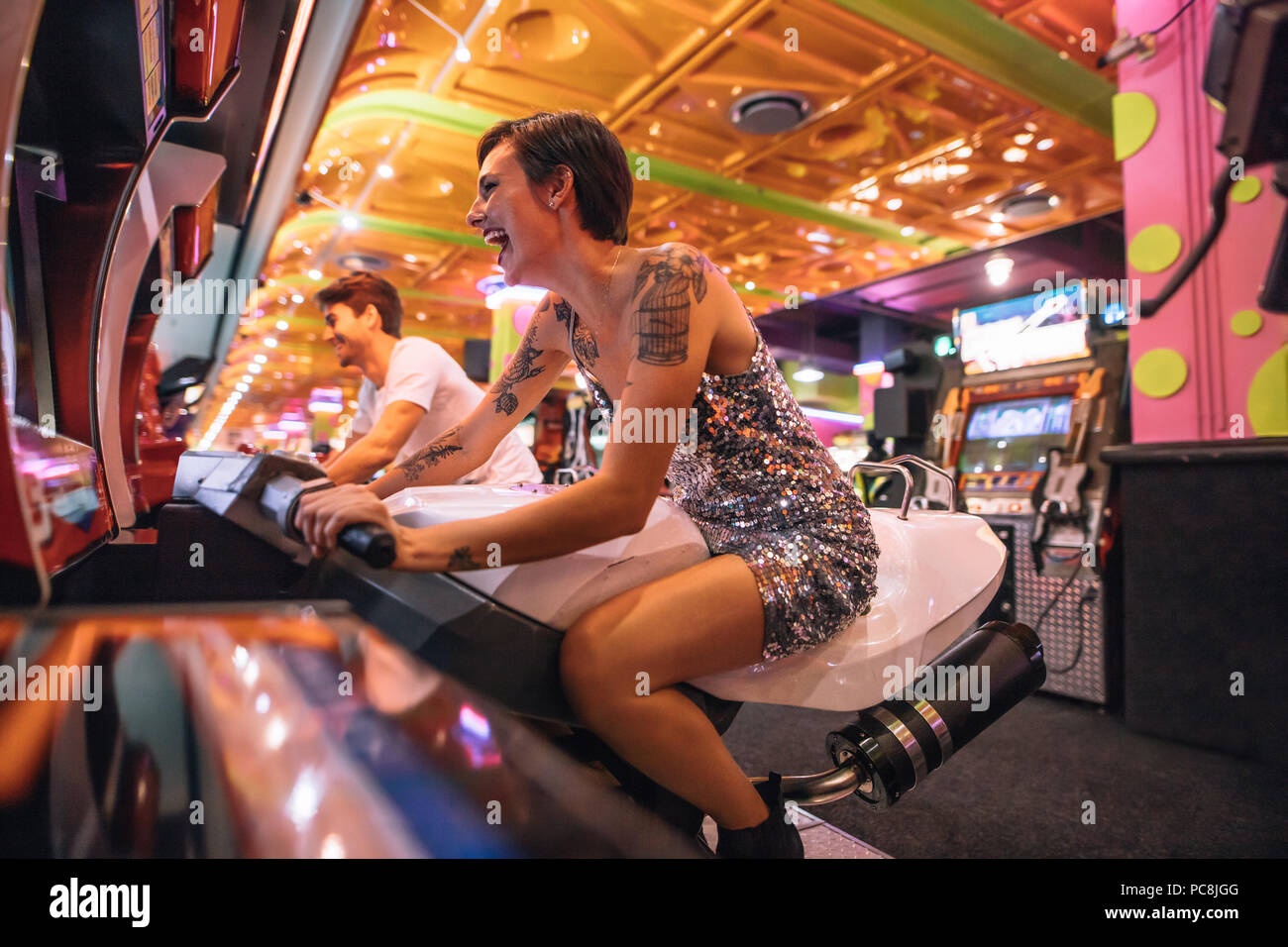 Happy couple having fun playing arcade racing games at a gaming parlour. Excited woman playing a racing game sitting on an arcade racing bike. - Stock Image