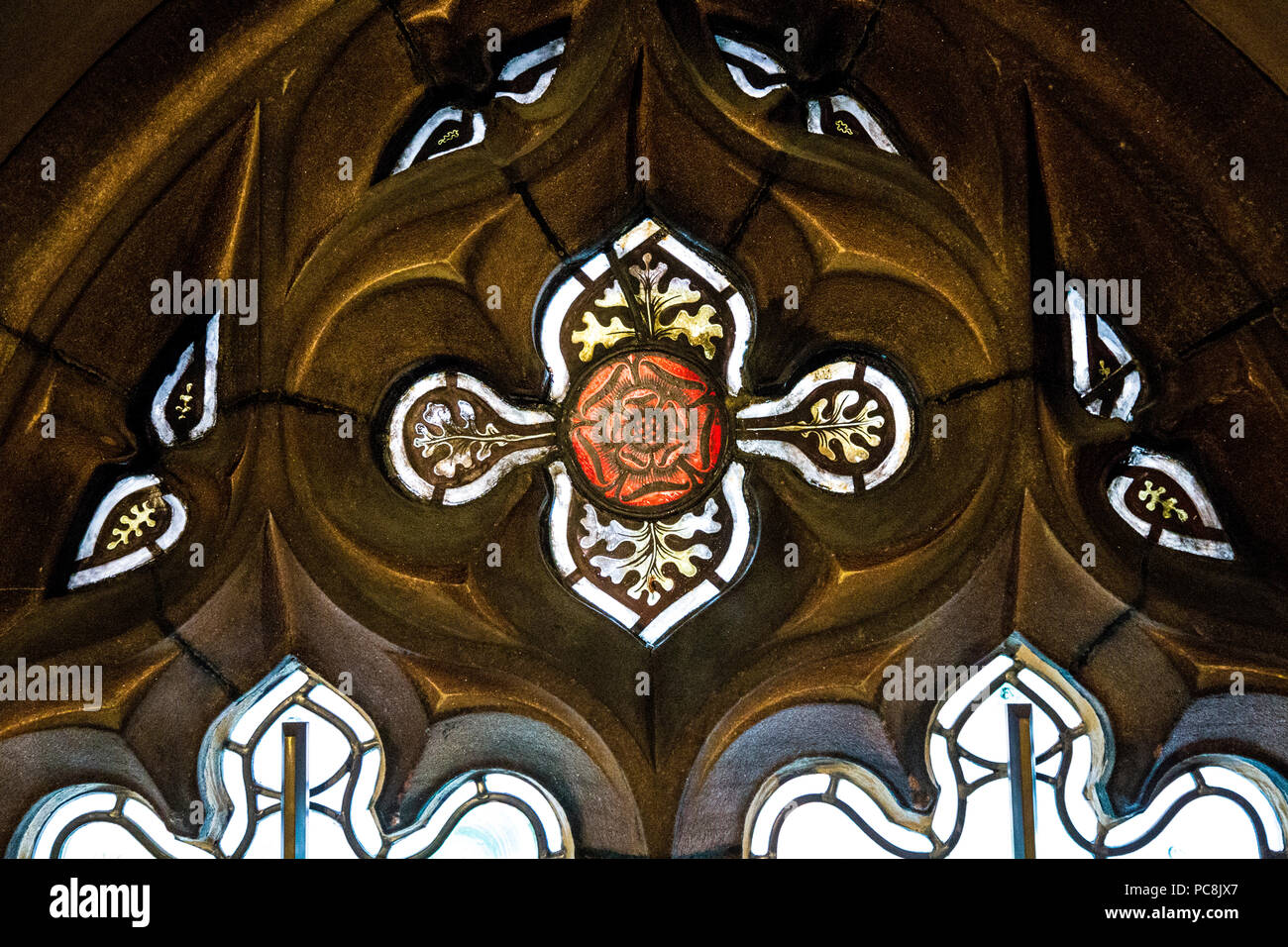 A red rose decorative stained glass window in a sandstone frame at John Rylands Library, Manchester, UK Stock Photo