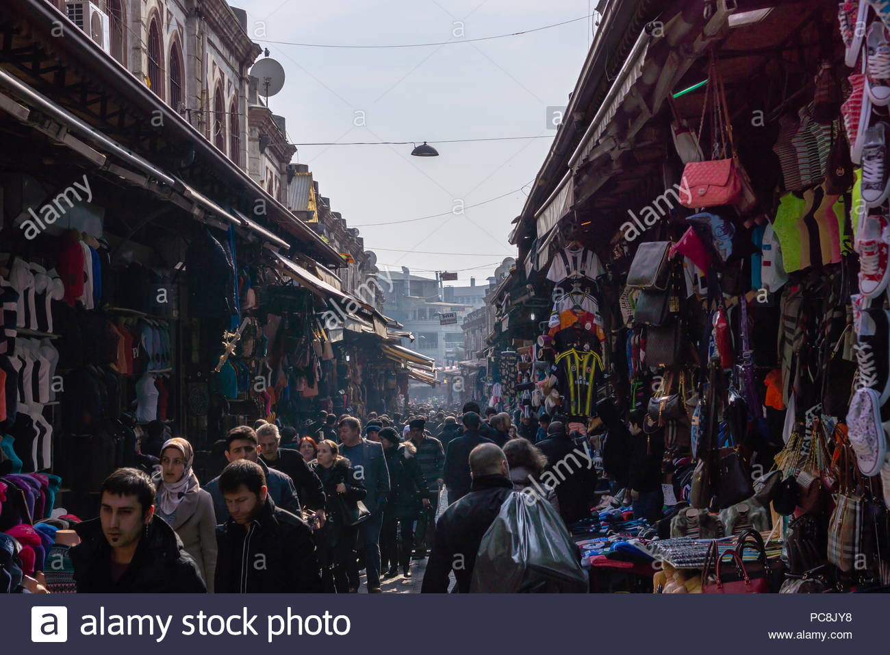 A busy street market in Istanbul where locals and tourists are going about their daily life and shopping on a cold winter morning. - Stock Image